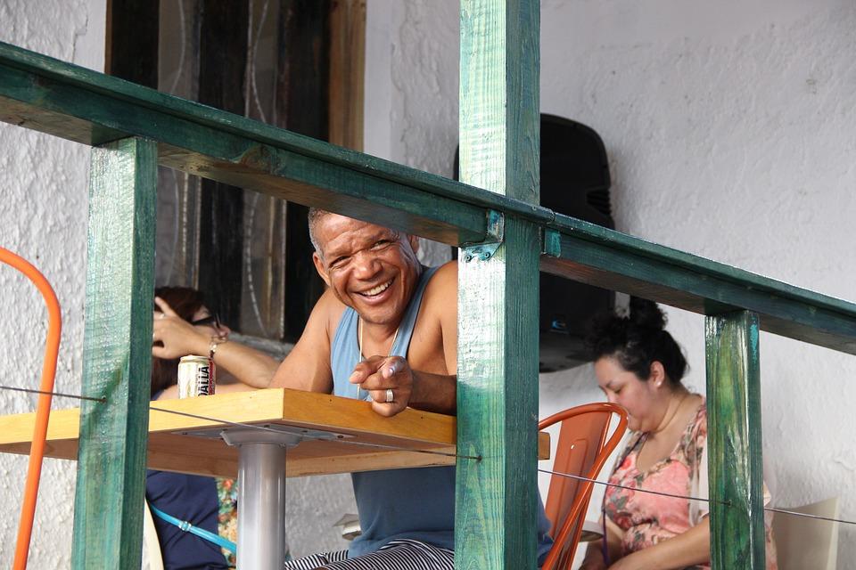 Un hombre sonriendo en la terraza junto a su mujer