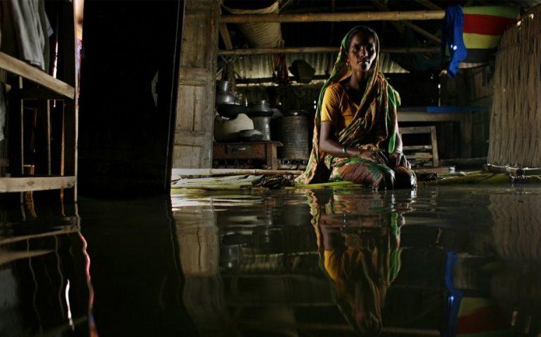 Rubia sentada en una balsa de plátano dentro de su casa que está inundada de agua en Bangladesh - Foto: Abir Abdullah